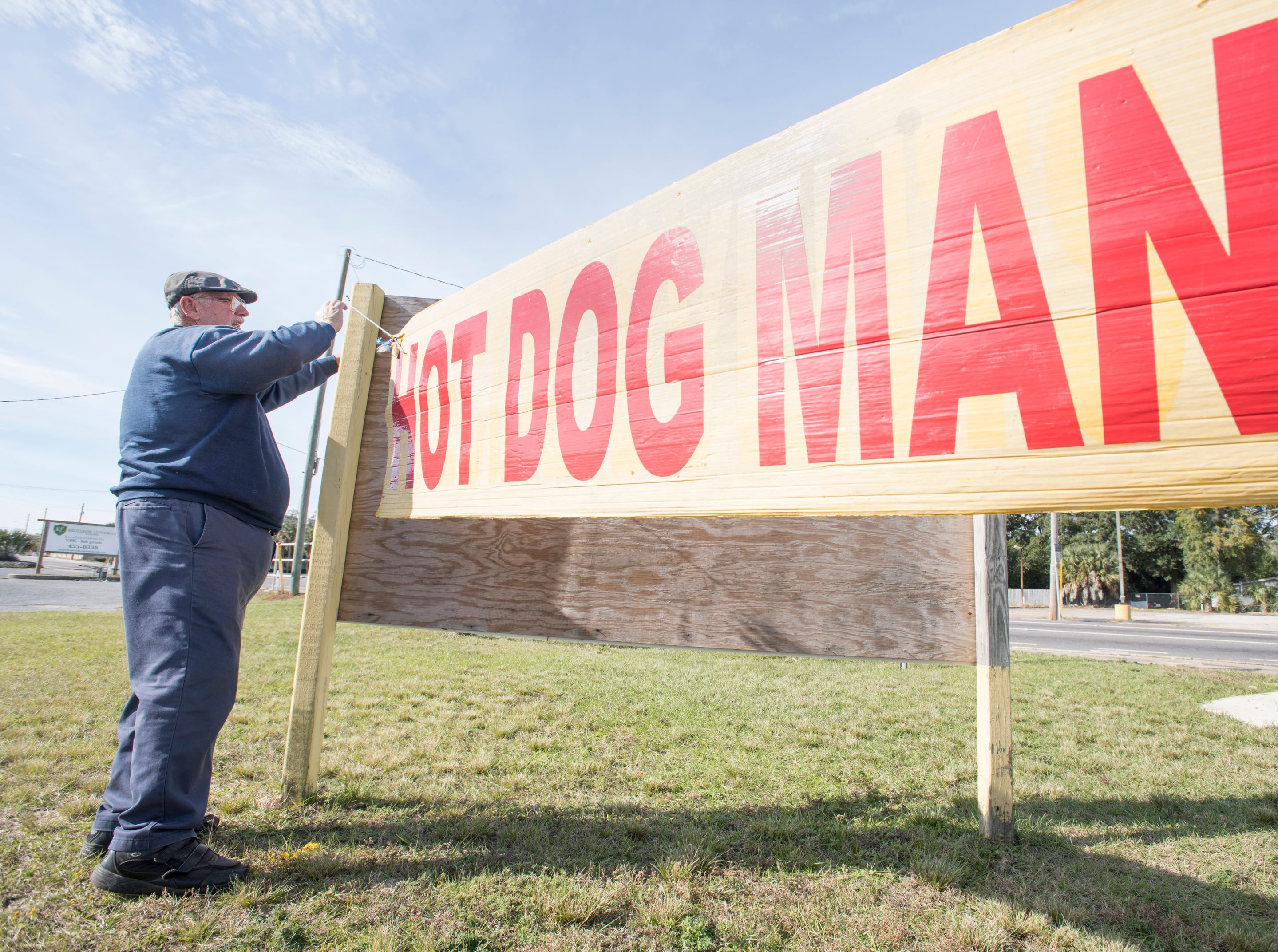 "Owner Ray Gluszek hangs a ""Hot Dog Man"" sign at his hot dog stand on Barrancas Avenue in Warrington on Thursday, December 6, 2018."