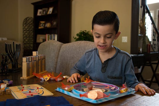 Judah Garcia plays with a dreidel while his family prepares for Hannukah on  Dec. 1, 2018.