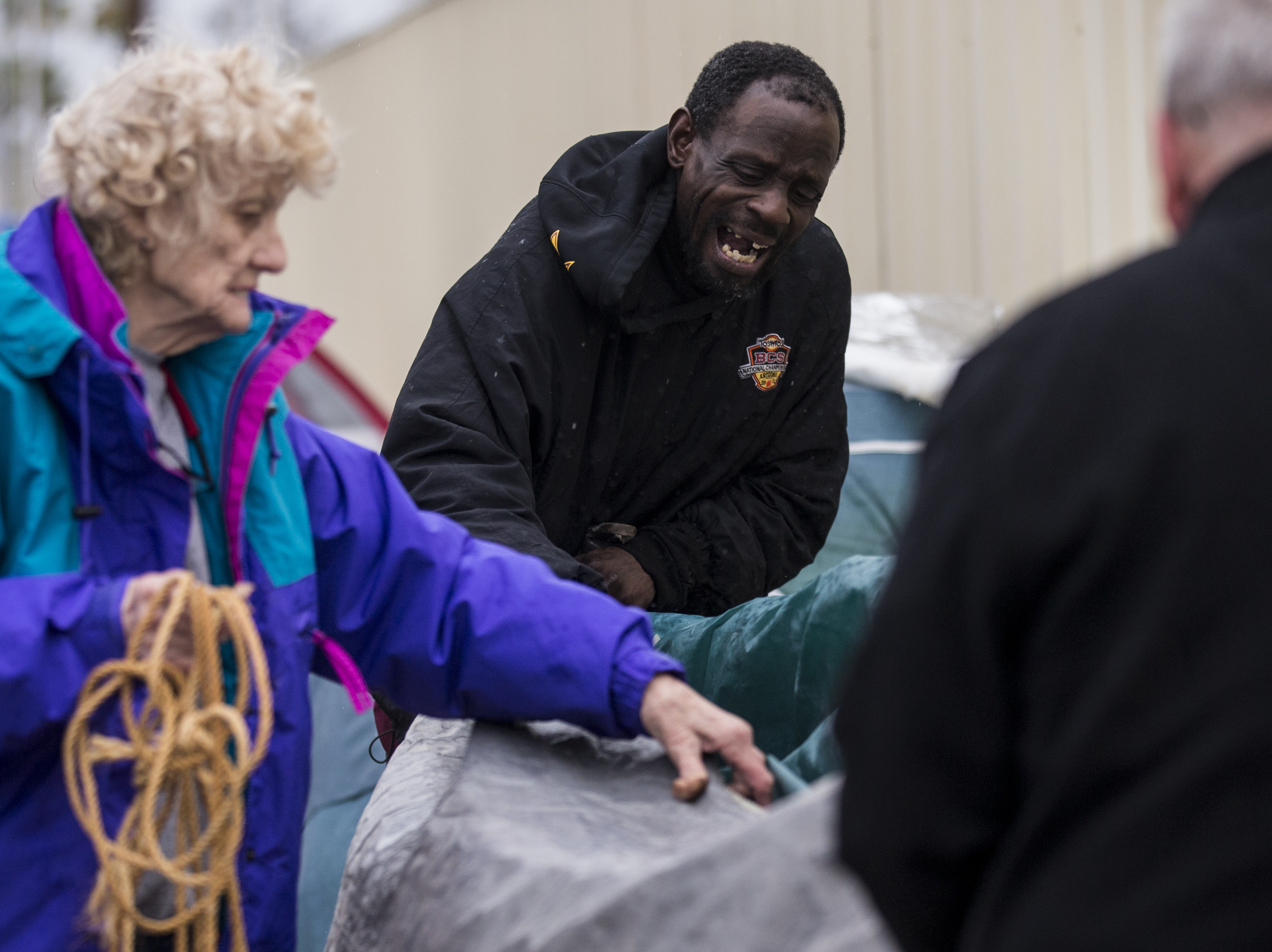Hosea Williams (center) helps Linda Lou Harris and Larry Downes break down a tent after waiting in line to get free dental work on Dec. 6, 2018, at the Arizona State Fairgrounds in Phoenix. The group's things got soaked by the rain and they decided they would come back next year.