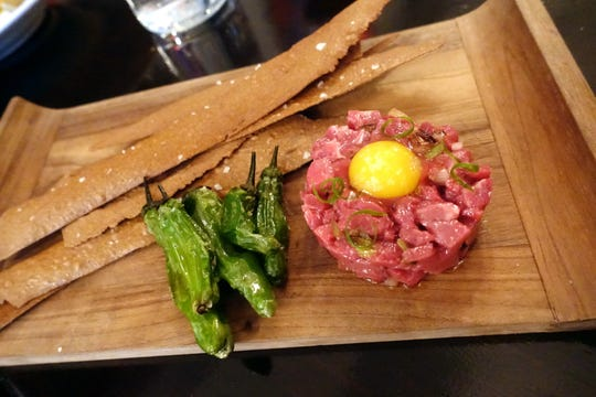 Bison tartare with quail egg yolk, i'itoi onion, prickly pear, shishito peppers and mesquite lavosh at Confluence in Carefree, AZ.