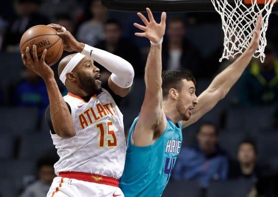 Atlanta Hawks' Vince Carter (15) grabs a pass as Charlotte Hornets' Frank Kaminsky (44) defends during the first half of an NBA basketball game in Charlotte, N.C., Wednesday, Nov. 28, 2018. (AP Photo/Chuck Burton)