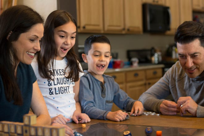 Amanda Garcia, Halle Garcia, Judah Garcia and Joseph Garcia participate in a family dreidel-spinning competition.