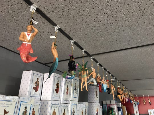Whozitz & Whatzitz mermen figures hanging from their store ceiling.