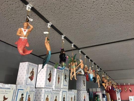 Whozitz & Whatzitz mermen figures hanging from their store ceiling.