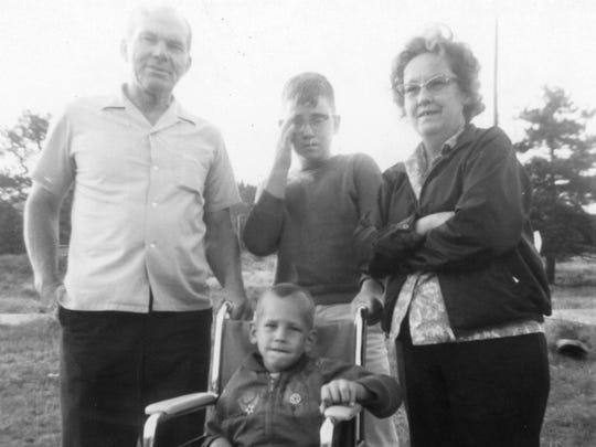 Randall Howe (center, at age 3 or 4) with his adopted father, brother and mother.