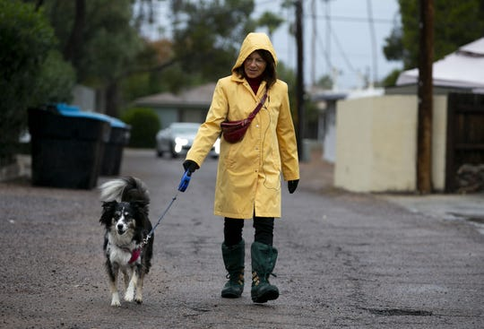 "Jan Kallas takes her dog ""Lizzy Borden Collie"" for a walk in light rain through an alleyway in Phoenix on Dec. 6, 2018."