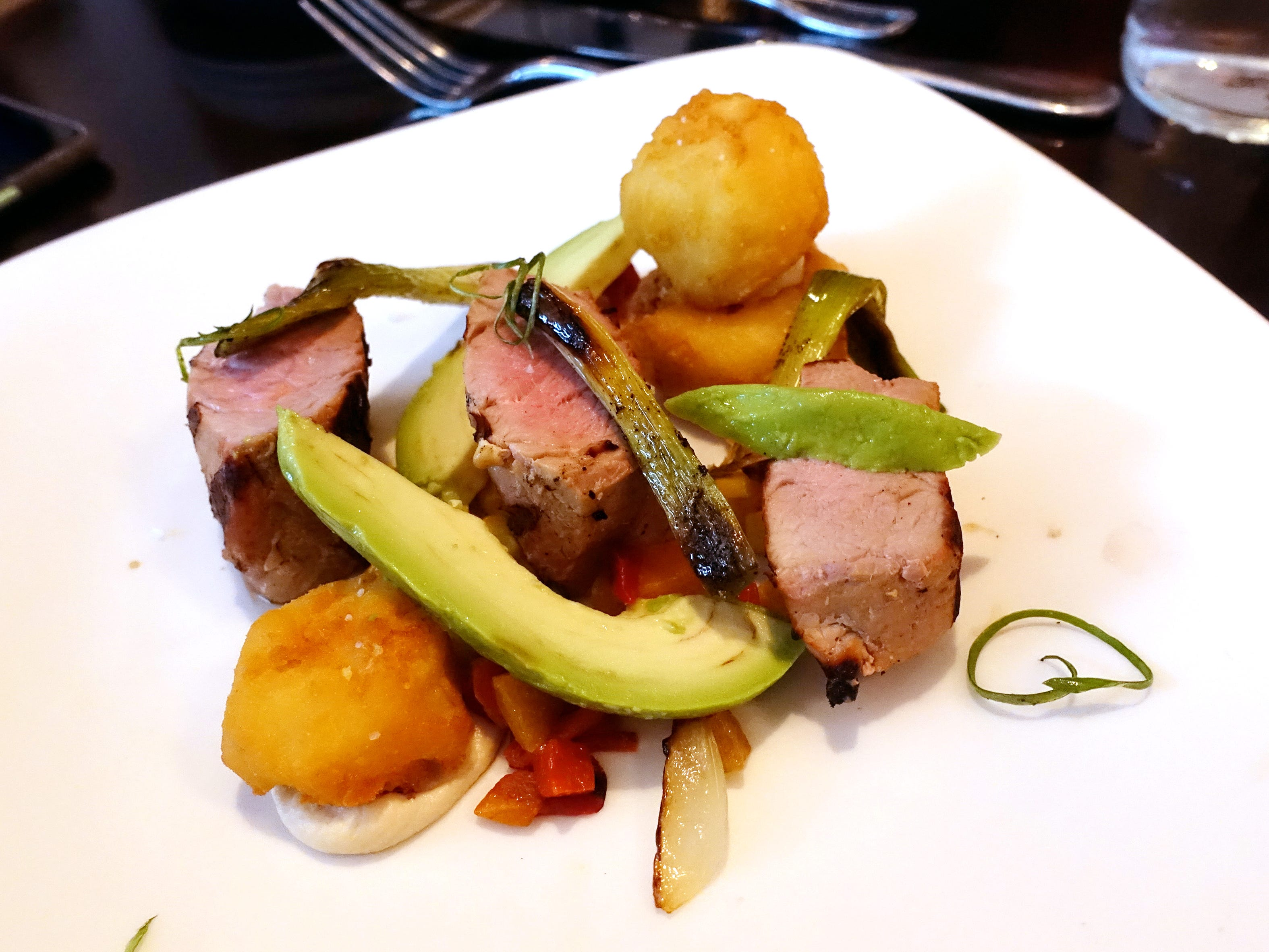 Pork tenderloin with corn, sweet peppers, polenta, pine nuts, scallion, avocado and bacon at Confluence in Carefree, AZ.
