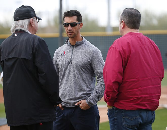 Diamondbacks General Manager Mike Hazen (center) talks with Arizona Owner Ken Kendrick (left) and team President and CEO Derrick Hall during the first day of full-squad spring training workouts on Feb. 19 at Salt River Fields.