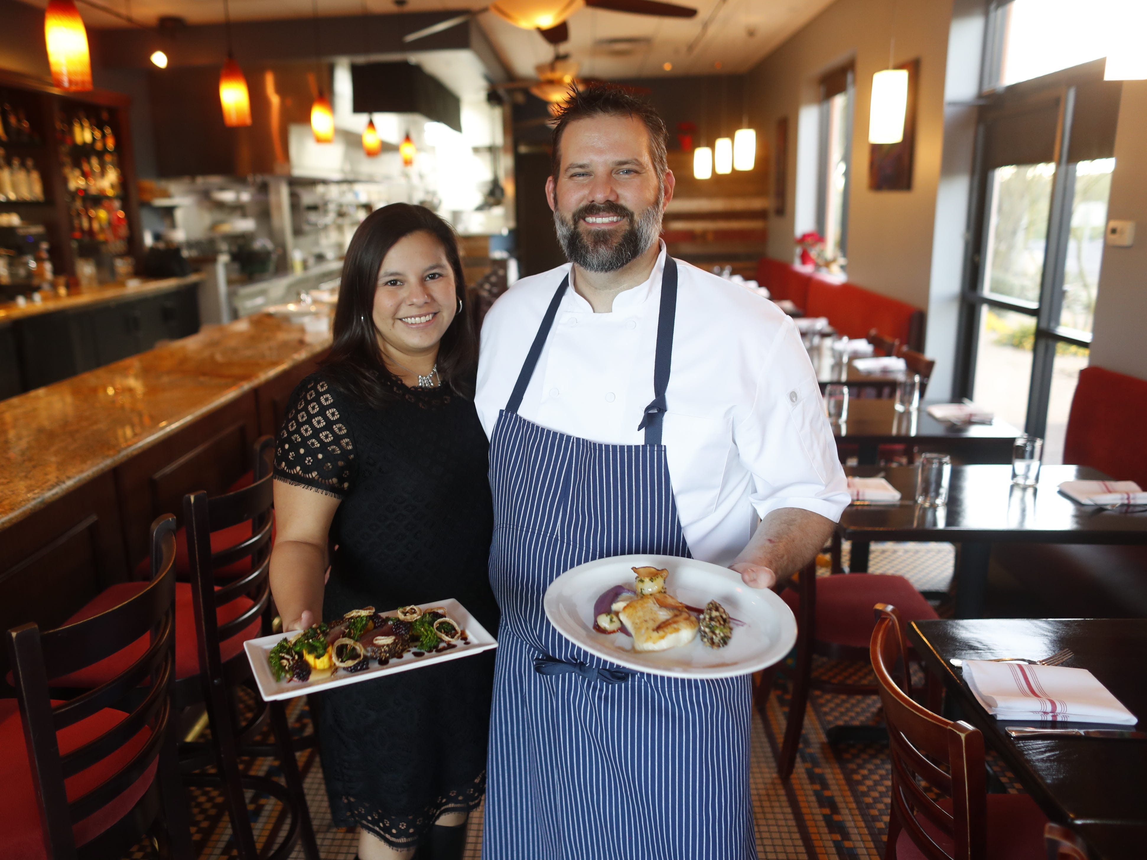 Chef Brandon Gauthier and his wife Victoria, house manager, hold two dishes, venison au poivre and black cod with yuba, at Confluence in Carefree on Dec. 3, 2018.