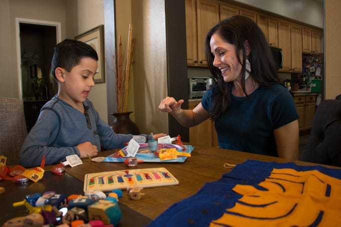 Judah Garcia and his mother, Amanda Garcia, play with a dreidel while decorating for Hanukkah on Dec. 1, 2018.