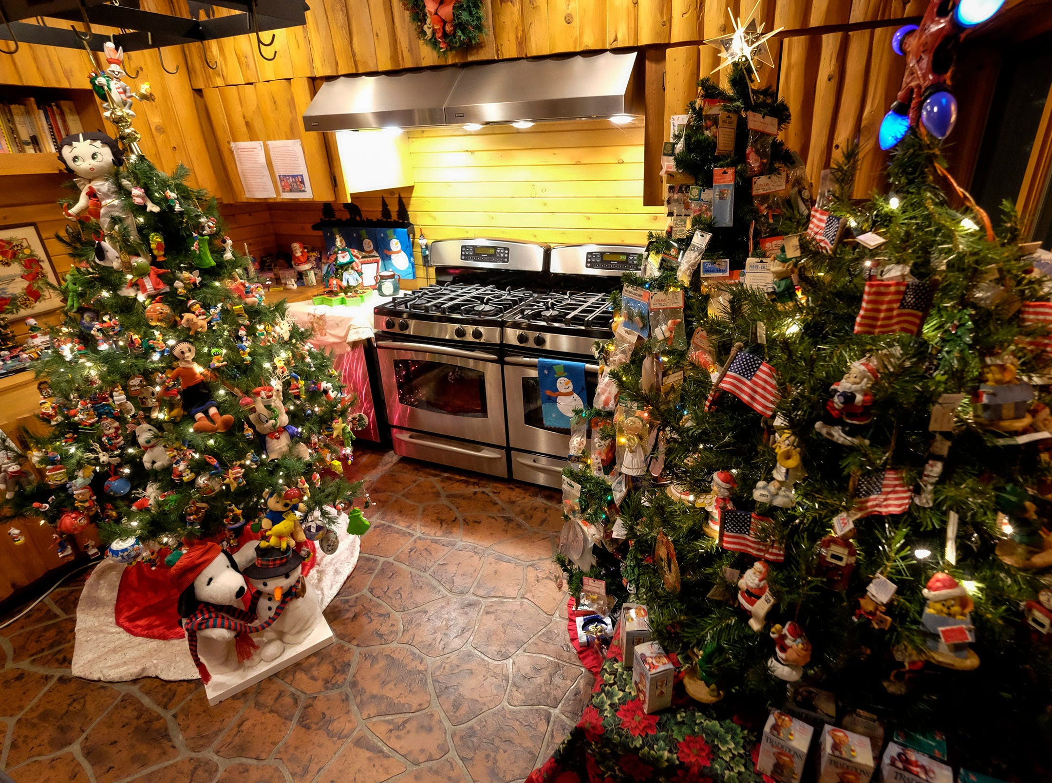 Themed Christmas trees are arranged in one of the kitchens of Al and Diane Kodet's home, where the annual History of the Christmas Tree Walk is held in Algonac.