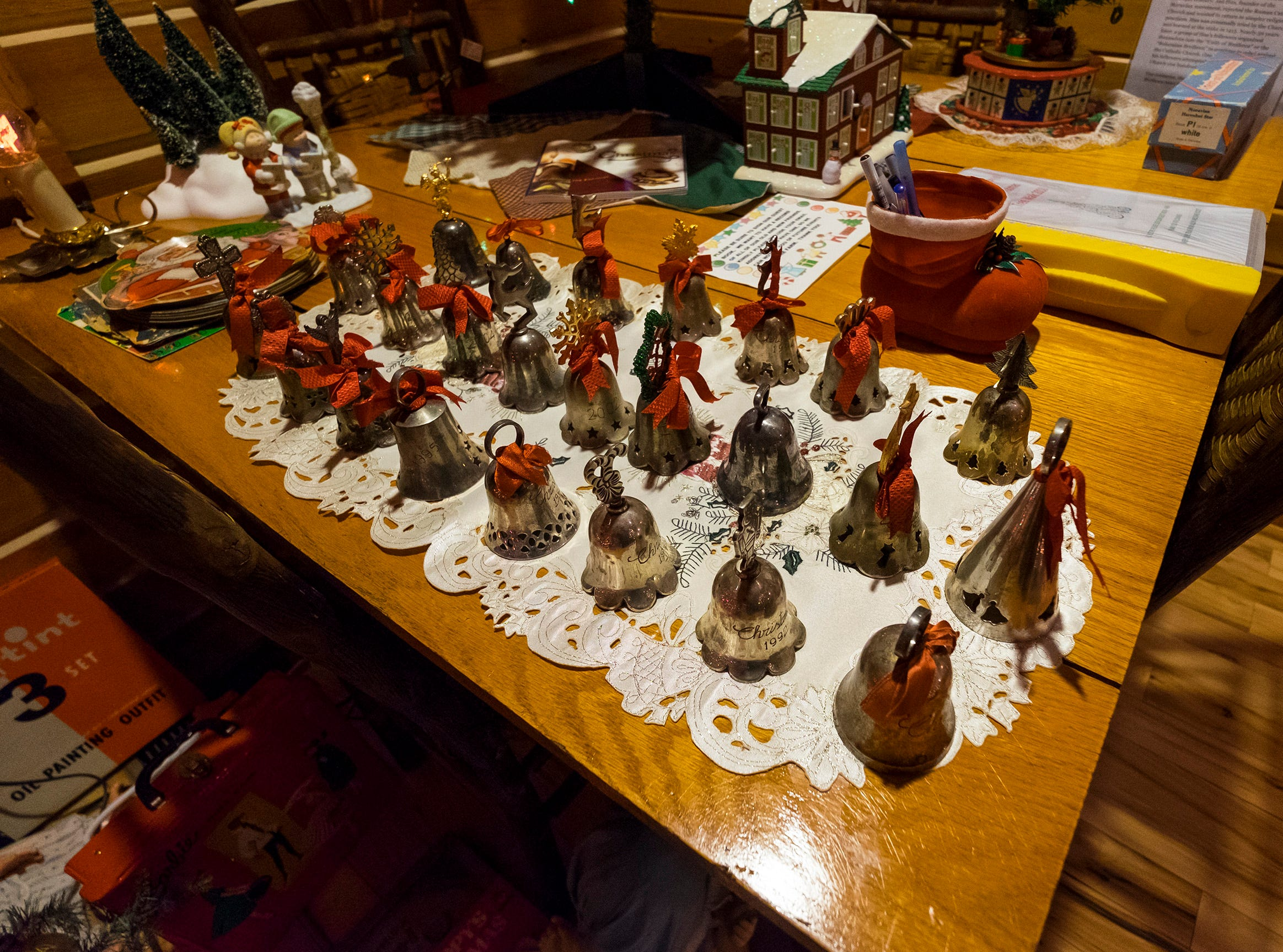 An assortment of hand bells are arranged on a table for the annual History of the Christmas Tree Walk at Al and Diane Kodet's home in Algonac.
