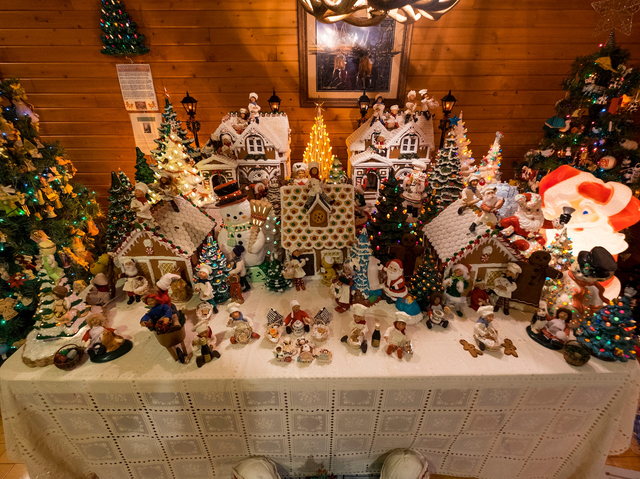 Gingerbread houses sit on a table near decorated Christmas trees for the annual History of the Christmas Tree Walk at Al and Diane Kodet's Algonac home.