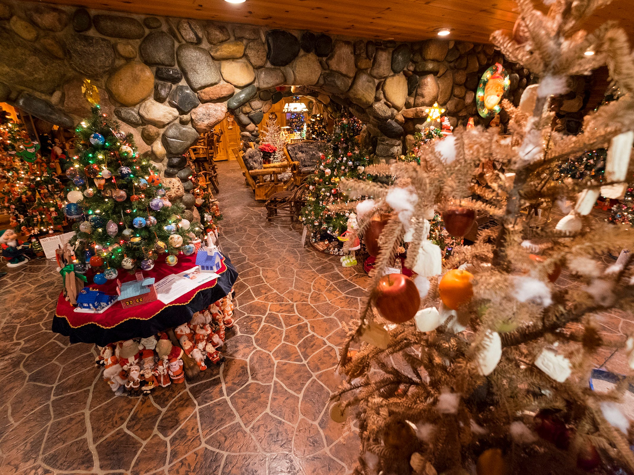 Christmas trees decorated for different themes are arranged in the basement of Al and Diane Kodet's Algonac home, where the annual History of the Christmas Tree Walk is held.