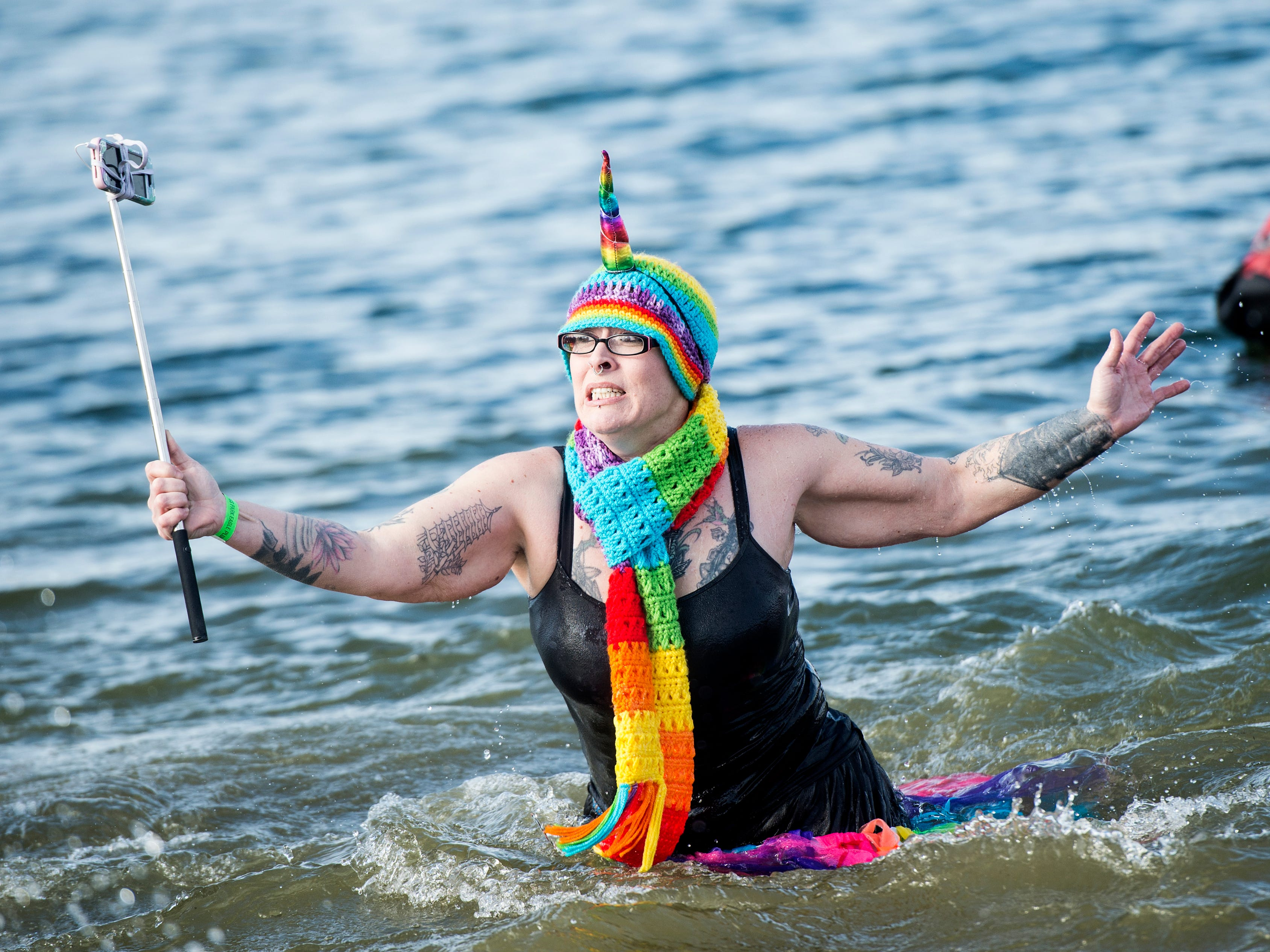 A participant in the eagle plunge reacts to the cold water after running in while holding a selfie stick. The water was measured at 34-degrees, Saturday, Jan. 27, 2018. The Codorus annual Winter Festival was full of different events and attractions, including ice carving, chainsaw carving, the eagle plunge, horse-drawn carriage rides and music.