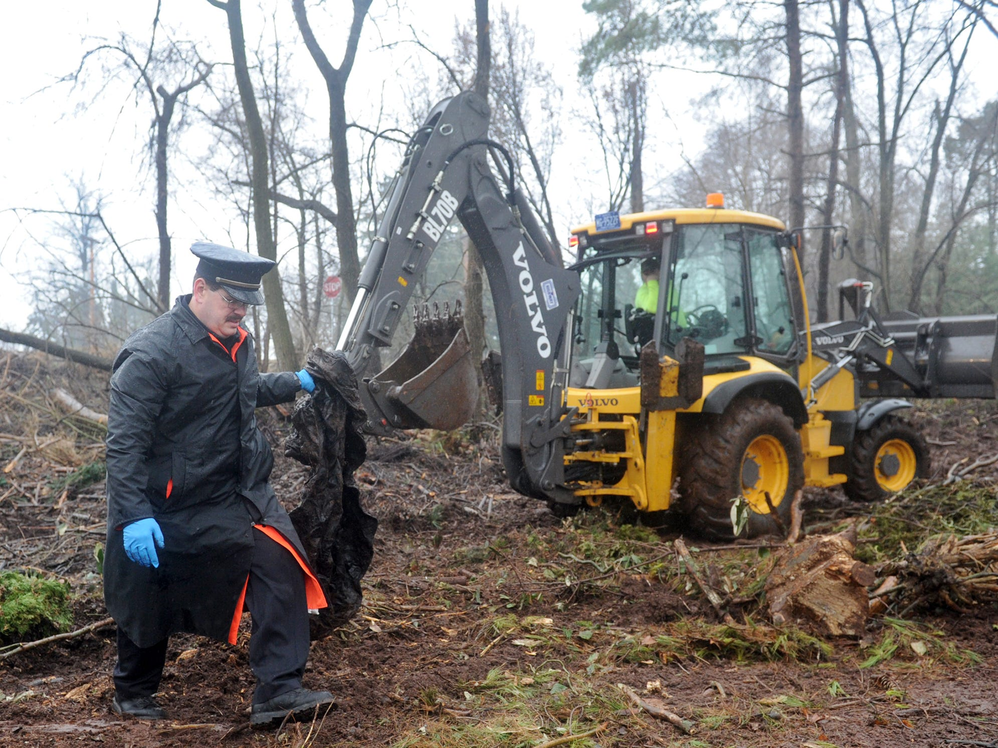 Officer Lance Krout with the West Manchester Township police department helps a member of the West Manchester Township maintenance crew investigate and clear out debris in a wooded area in West Manchester Township on Monday, April 7, 2014. The location was where a body was found last year and the police were there as part of an ongoing effort to identify the remains, West Manchester Township Chief Arthur Smith said. The investigation began Nov. 18, 2013 when tree trimmers working at Haviland and Loucks roads spotted a skull and called police.