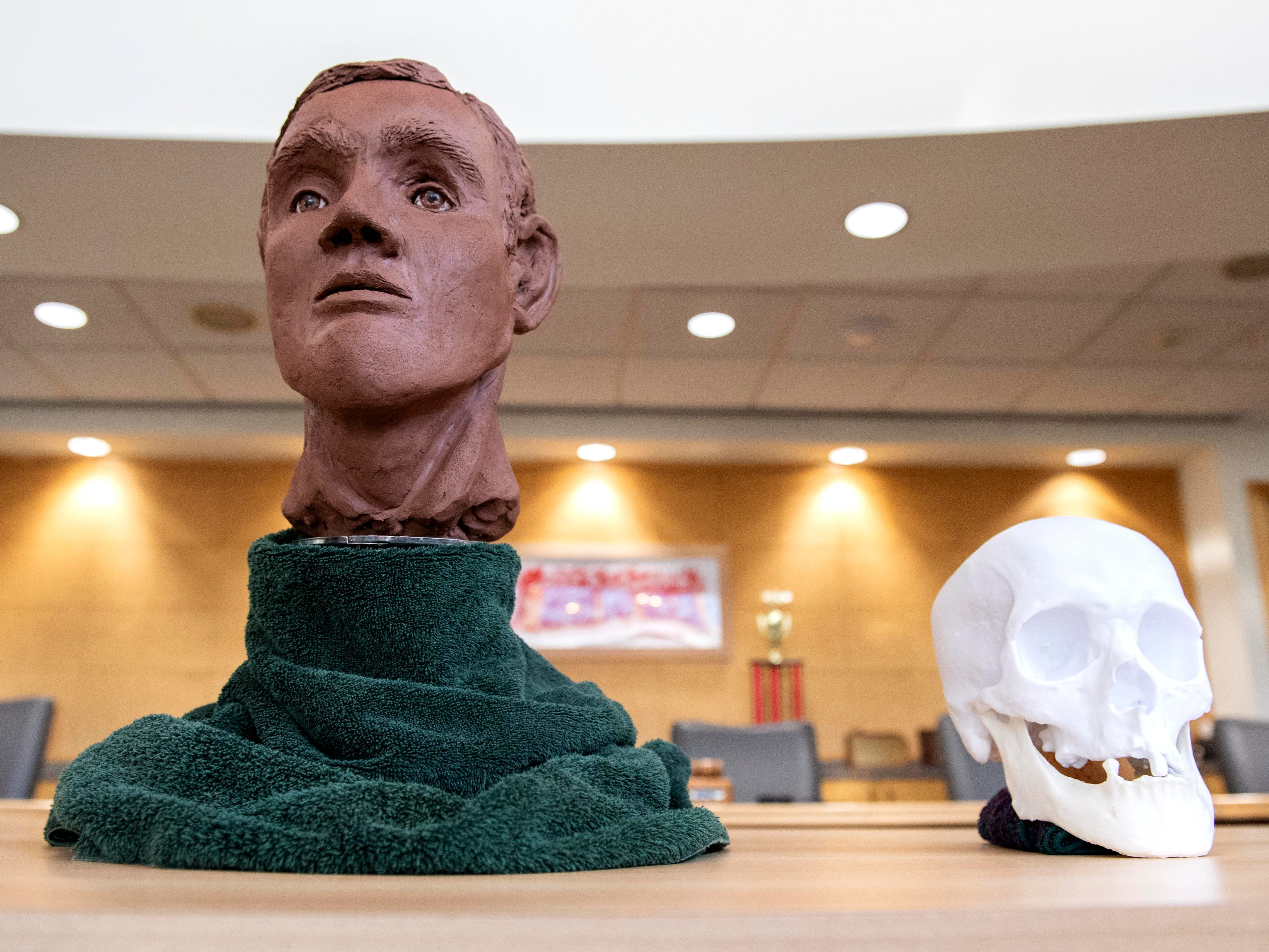 A clay bust, depicting what a cold case victim might have looked like, along with a 3D-printed skull, created by forensic artist Jenny Kenyon, sit in the West Manchester Township building during a news conference. The victim's skeletal remains were found at the intersection of Loucks and Haviland roads in November 2013.