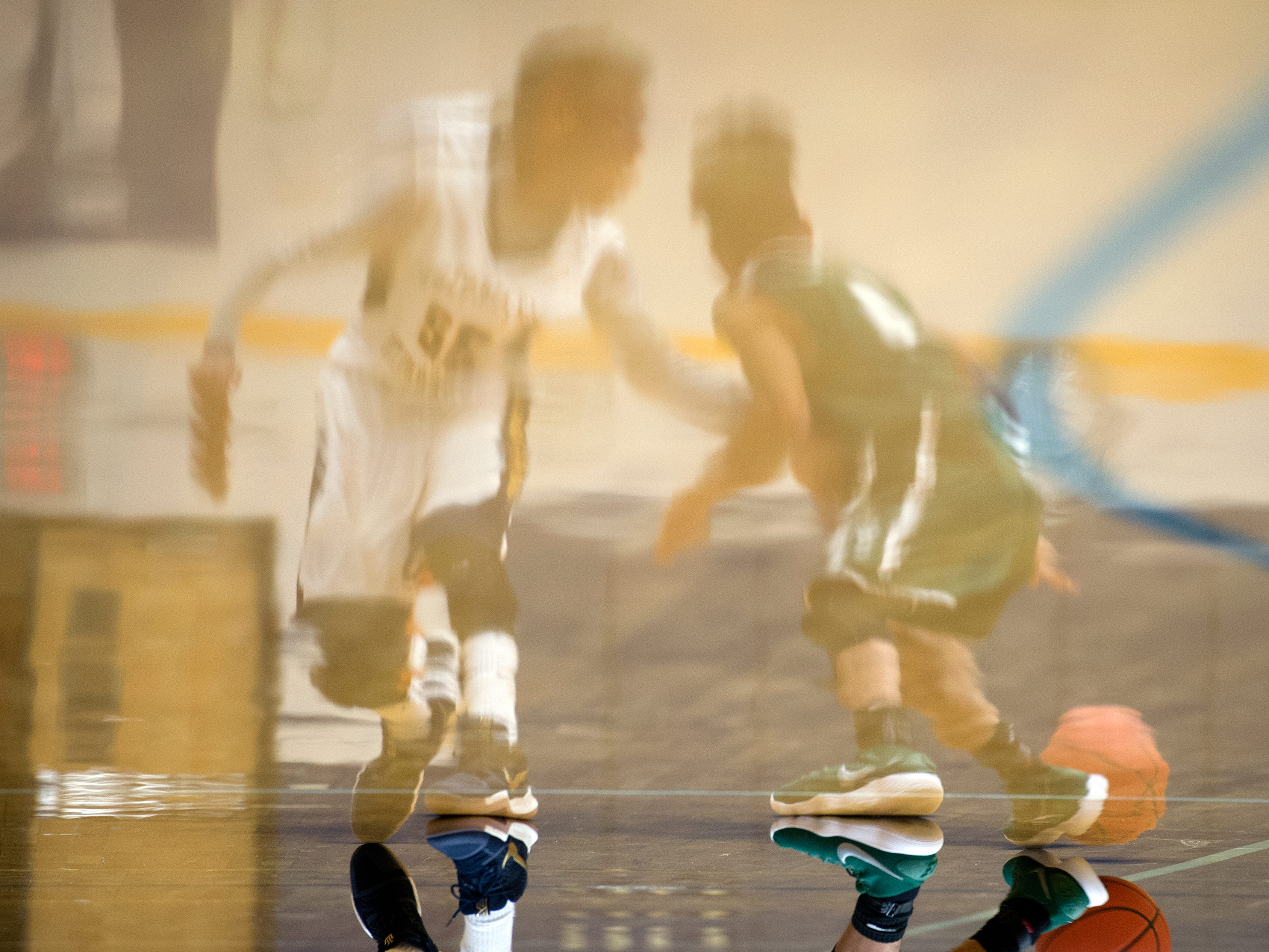 Reflections of basketball players are seen on the court, Wednesday, Jan. 10, 2018. The Littlestown Bolts beat the York County Tech Spartans, 61-44.