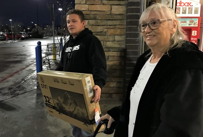 "Patty Whitehill of Reno leaves Walmart with her grandson, Aurelio Sedano, and her new TV on Dec. 5, 2018. She had gone into the Reno store to make a layaway payment and found that a ""secret Santa"" had paid $46,000 of other people's layaway bills."