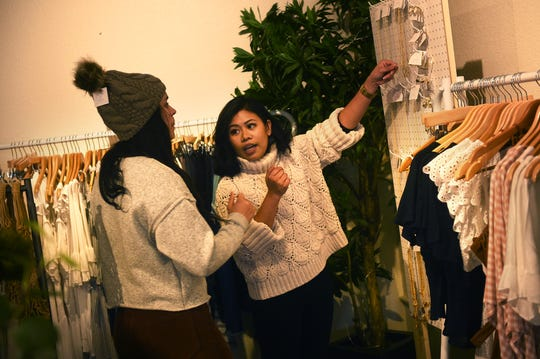 Joanna Cuenza, right, owner of Sittie & Sage clothing boutique in Midtown Reno, helps a customer in her store on Dec. 5, 2018.