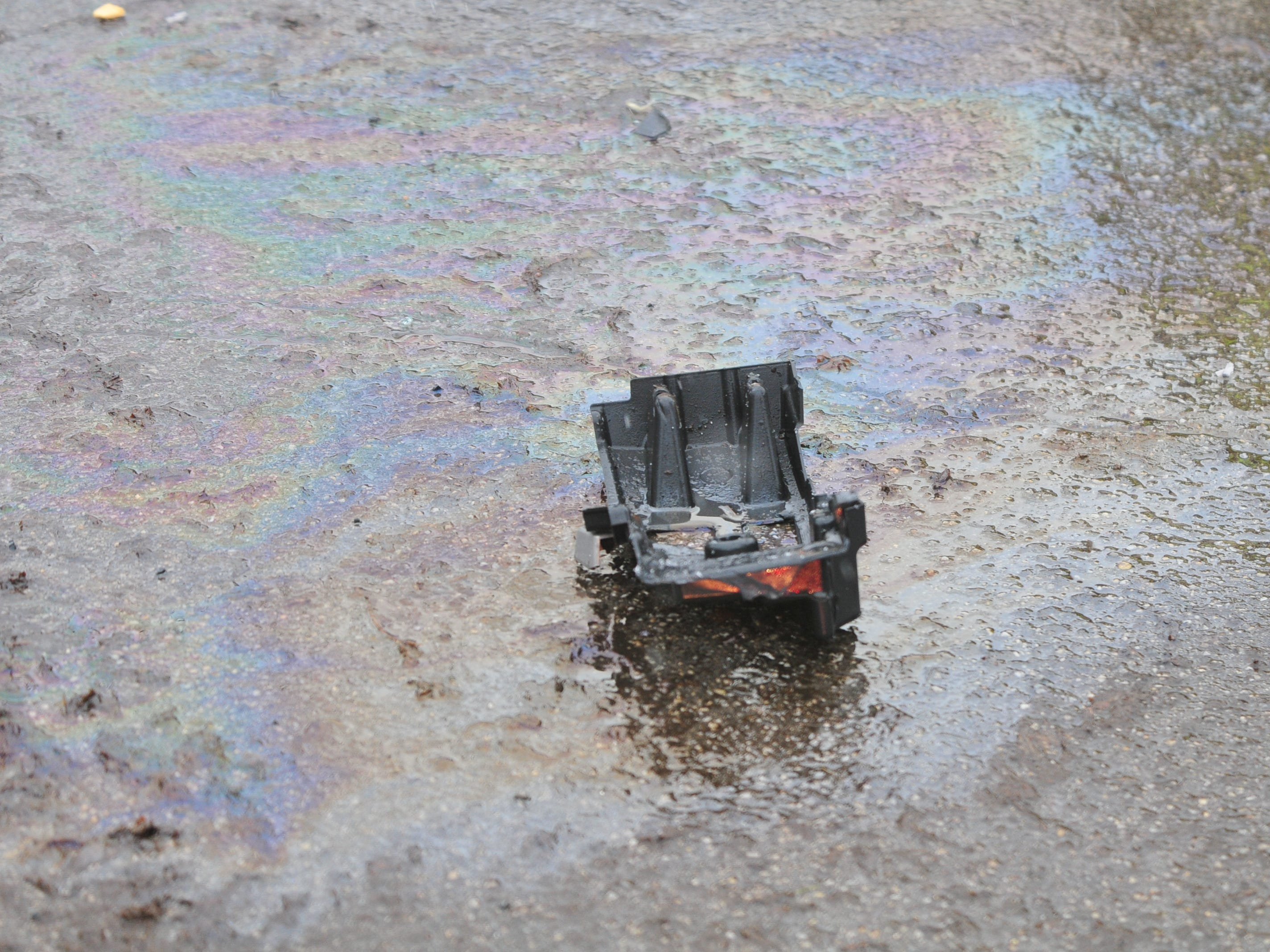 Debris from an accident sits in a colorful pattern made by fluids on the wet roadway Thursday on Richmond Avenue.