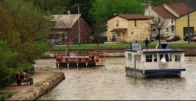 The Miss Apple Grove, a mule-towed boat run by the Apple Grove Inn at Medina, Orleans County, shares the Erie Canal in Medina with a boat that a family from Madison, Wisconsin, is vacationing on.