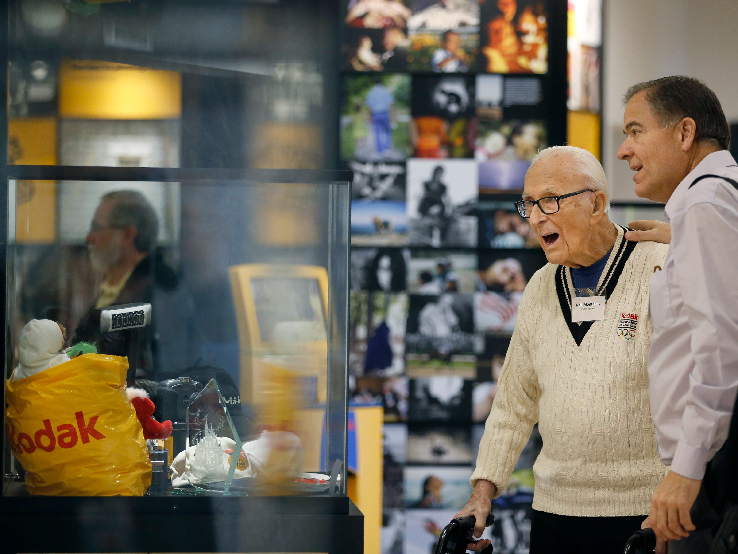 Kodak retiree and former photographer Neil Montanus, 91, walks through the exhibits with his son Jim during the Kodak Visitor Center Grand Opening. Montanus shot 55 of the 565 Coloramas throughout the years for the company, with some printed samples on display at the center.
