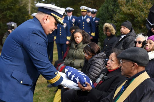 In this Dec. 5, 2018 photo, Rear Adm. Andrew Tiongson, commander First Coast Guard District, passes a folded American flag to a family member during funeral services for Olivia Hooker in White Plains, N.Y. Hooker, the first African-American woman to serve in the U.S. Coast Guard and one of the last survivors of a race riot in Oklahoma, has been laid to rest with military honors. Hooker passed away on Nov. 21, 2018, at the age of 103. (Petty Officer 3rd Class Steve Strohmaier/U.S. Coast Guard via AP)