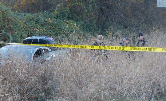 Crime scene investigators survey the scene of a Thursday officer-involved shooting off Interstate 5 south of Redding.