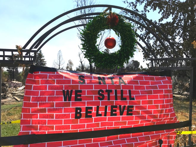 Neighbors put up this sign and display not long after the Carr Fire destroyed the Christmas House where it stood on Harlan Drive in Redding.
