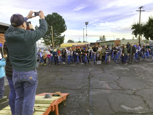 Tim Hill of Shasta Living Streets takes a group photo of adult Carr Fire survivors who received free bikes through the efforts of Mike Stewart of Giant Bicycles, Angie James of the Chain Gang Bike Shop and Redding Community Services Director Kim Niemer.
