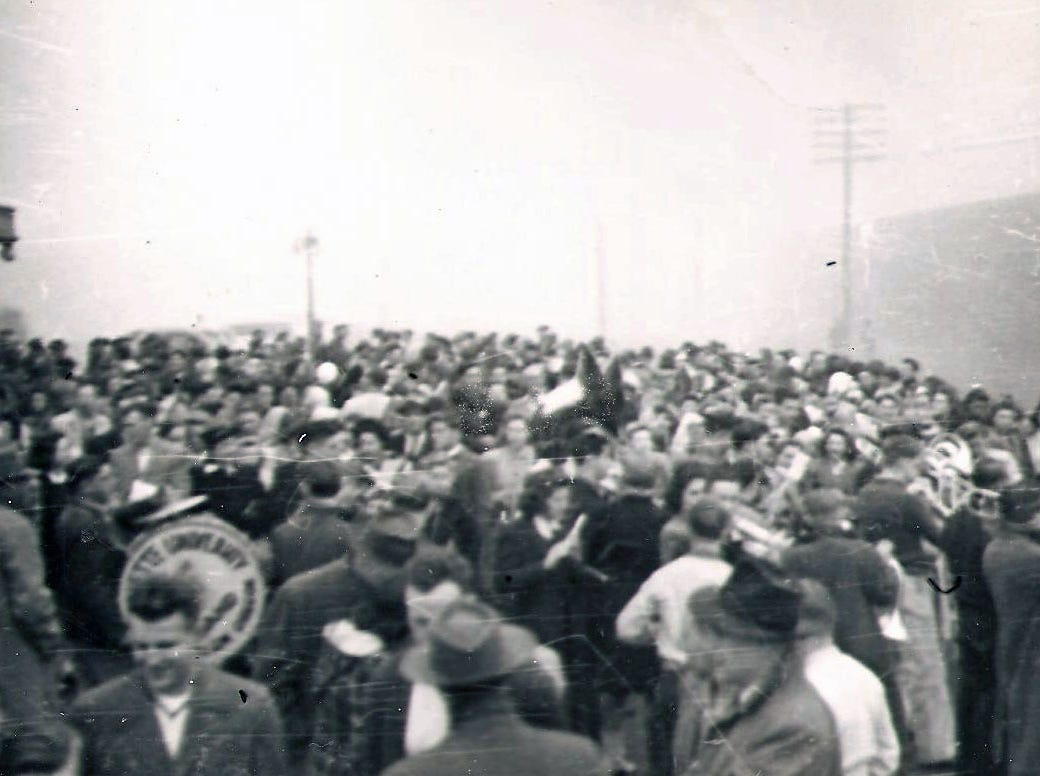 An estimated crowd of 1,000 people show up at the train station in Salem to welcome home the 1941 Willamette University football team, which was called into action after the attack on Pearl Harbor.
