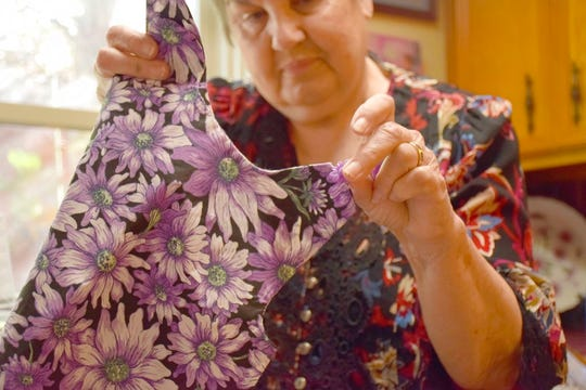In this Nov. 26, 2018 photo, Bernice Spell Bernice Spell shows the button she's considering sewing on the shoulder of a dress that she will donate to a local child, at her home that overlooks the lake behind her house in Lake Jackson, Texas. Since the hurricane hit last year, Spell has gotten up every morning and sewed shirts, dresses, jackets, shorts and pants for children in need 4 to 6 years old.