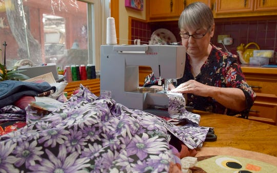 In this Nov. 26, 2018 photo, Bernice Spell sews at a table in her kitchen that overlooks the lake behind her house in Lake Jackson, Texas. Since the hurricane hit last year, Spell has gotten up every morning and sewed shirts, dresses, jackets, shorts and pants for children in need 4 to 6 years old.