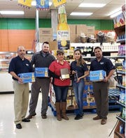 Daniel Castro, Samuel Calhoun and Fernando Reyes present La Azteca employees Rosie Vasquez and Vicky Gonzalez with an award at the store, 2028 N Bryant Blvd., Wednesday, Dec. 5, 2018.