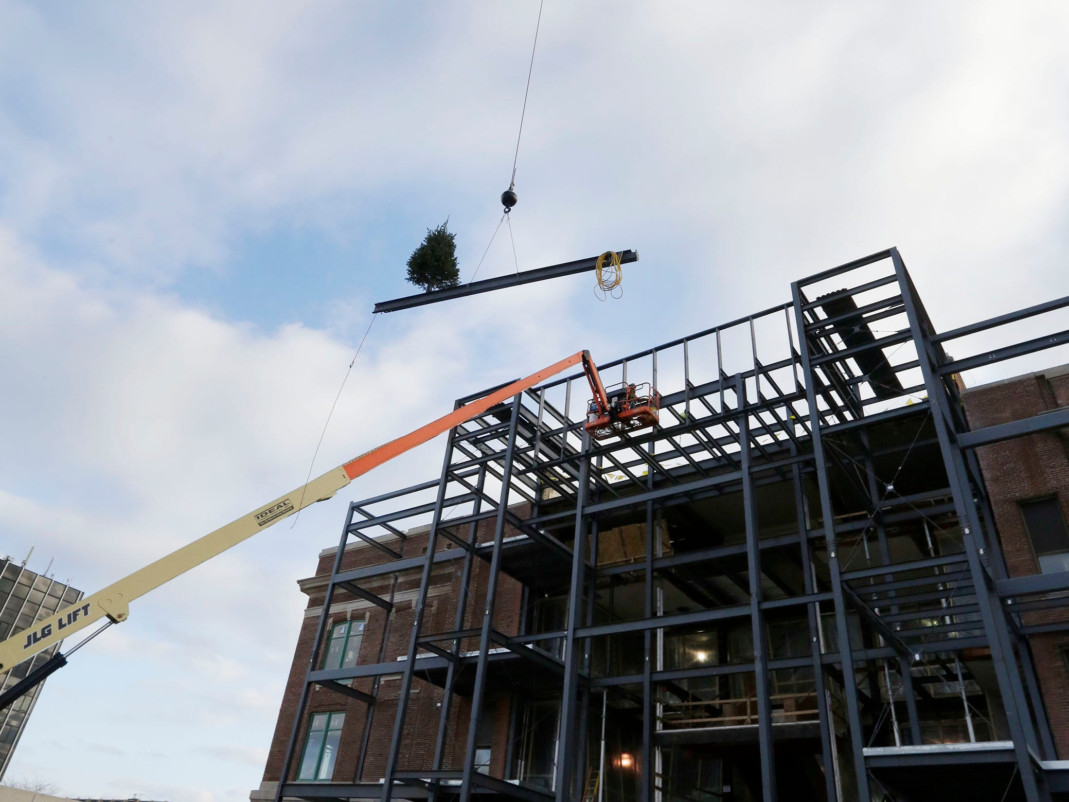 The last structural beam is elevated to the top of the new front at Sheboygan City Hall during a topping off ceremony, Wednesday, December 5, 2018, in Sheboygan, Wis.