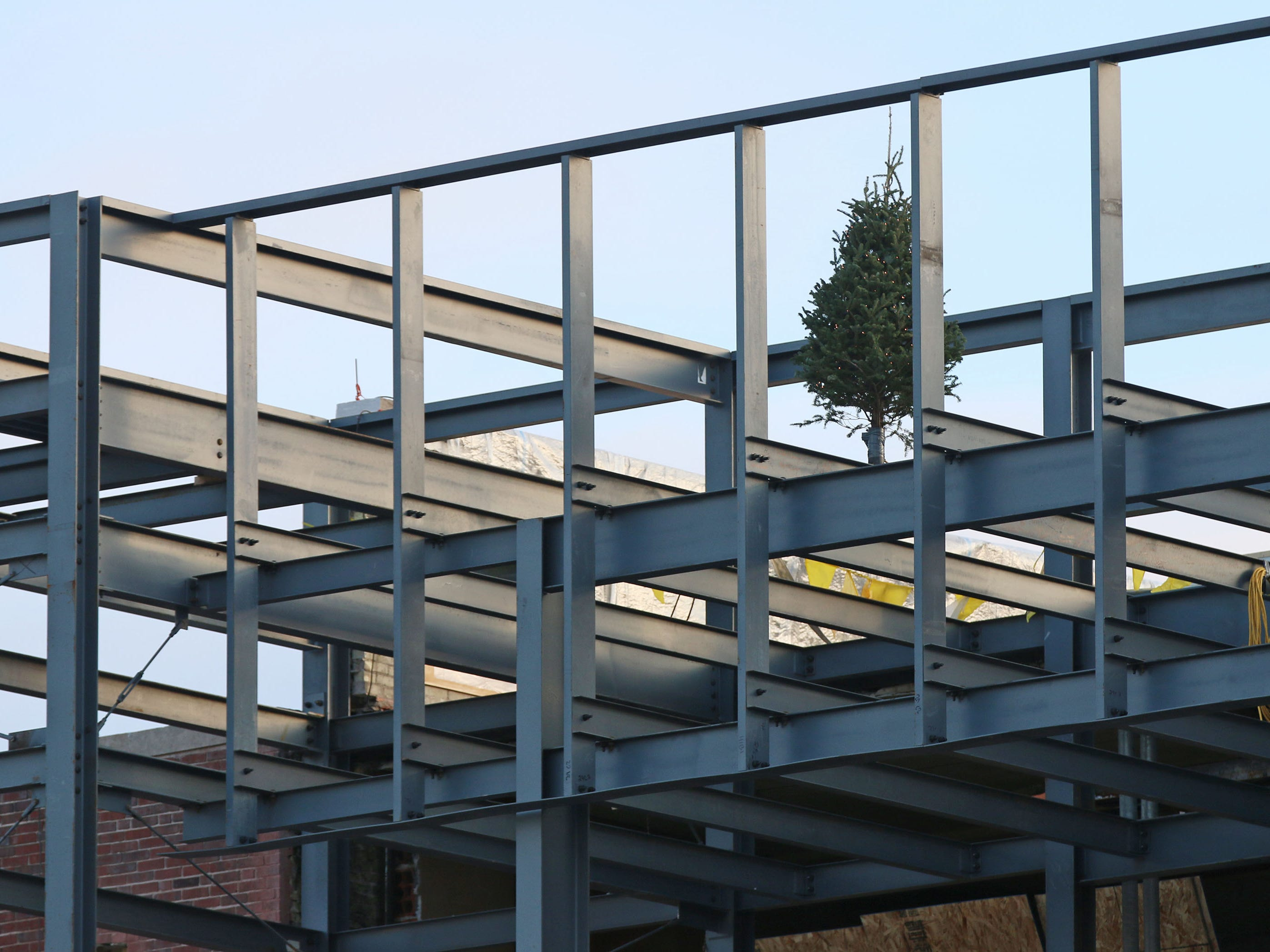 A Christmas tree is secured to a beam atop the Sheboygan City Hall, Wednesday, December 5, 2018, in Sheboygan, Wis. A topping off ceremony was held Wednesday in honor of the installation of the last structural beam for the 10.5 million dollar city hall renovation project.