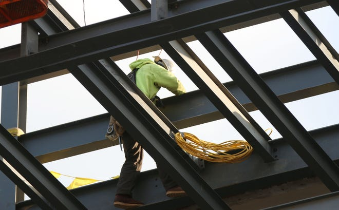 A construction worker secures a beam during the Sheboygan City Hall topping off ceremony, Wednesday, December 5, 2018, in Sheboygan, Wis.