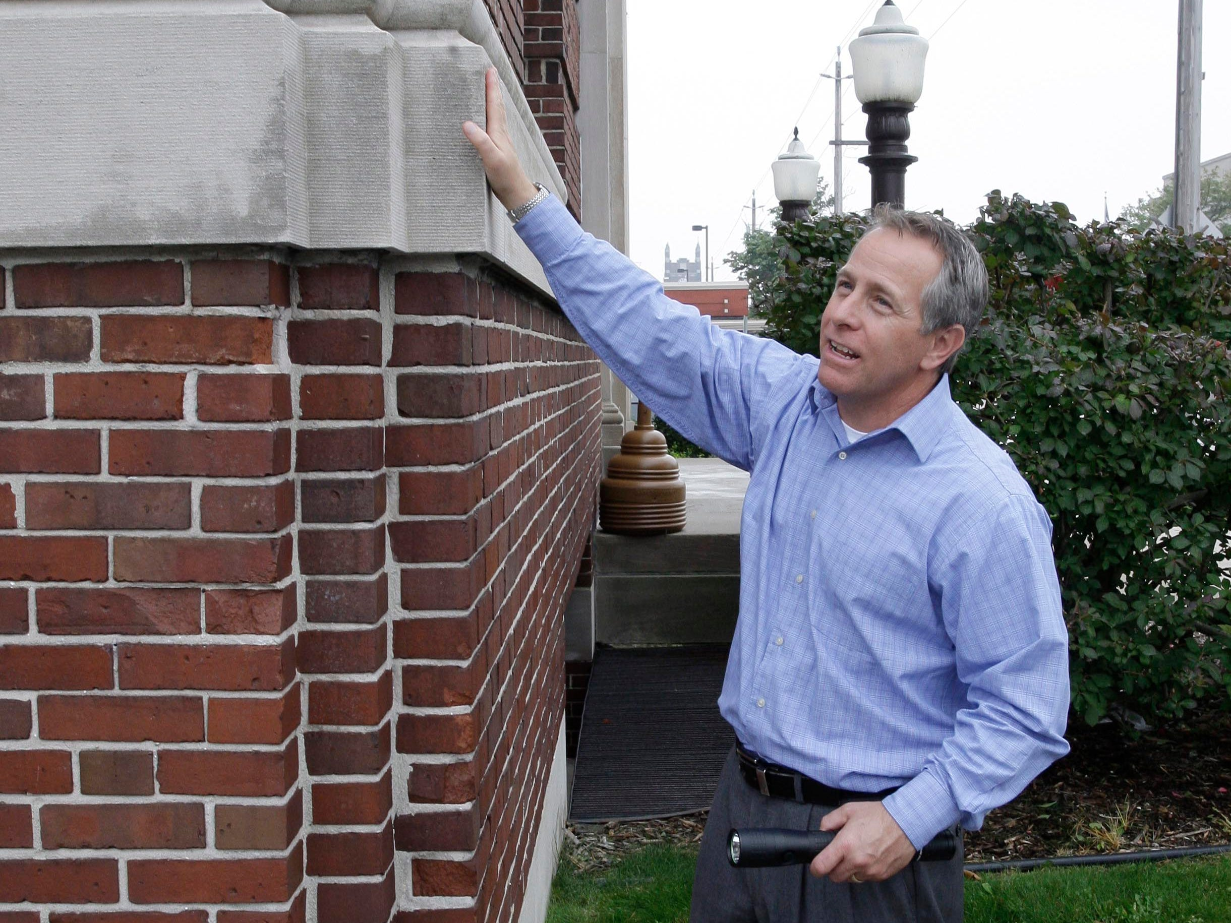 Director of Public Works David Biebel points out an architectural detail on the exterior of city hall, Thursday October 2, 2014, in Sheboygan, Wis.