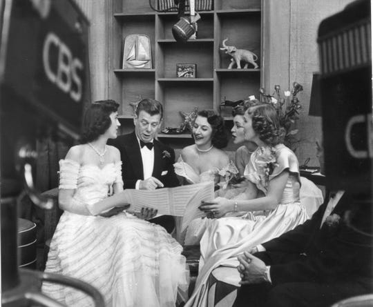 This is a handout photo of Authur Godfrey going over some sheet music with the Chordettes when they were at their apex of fame in the e