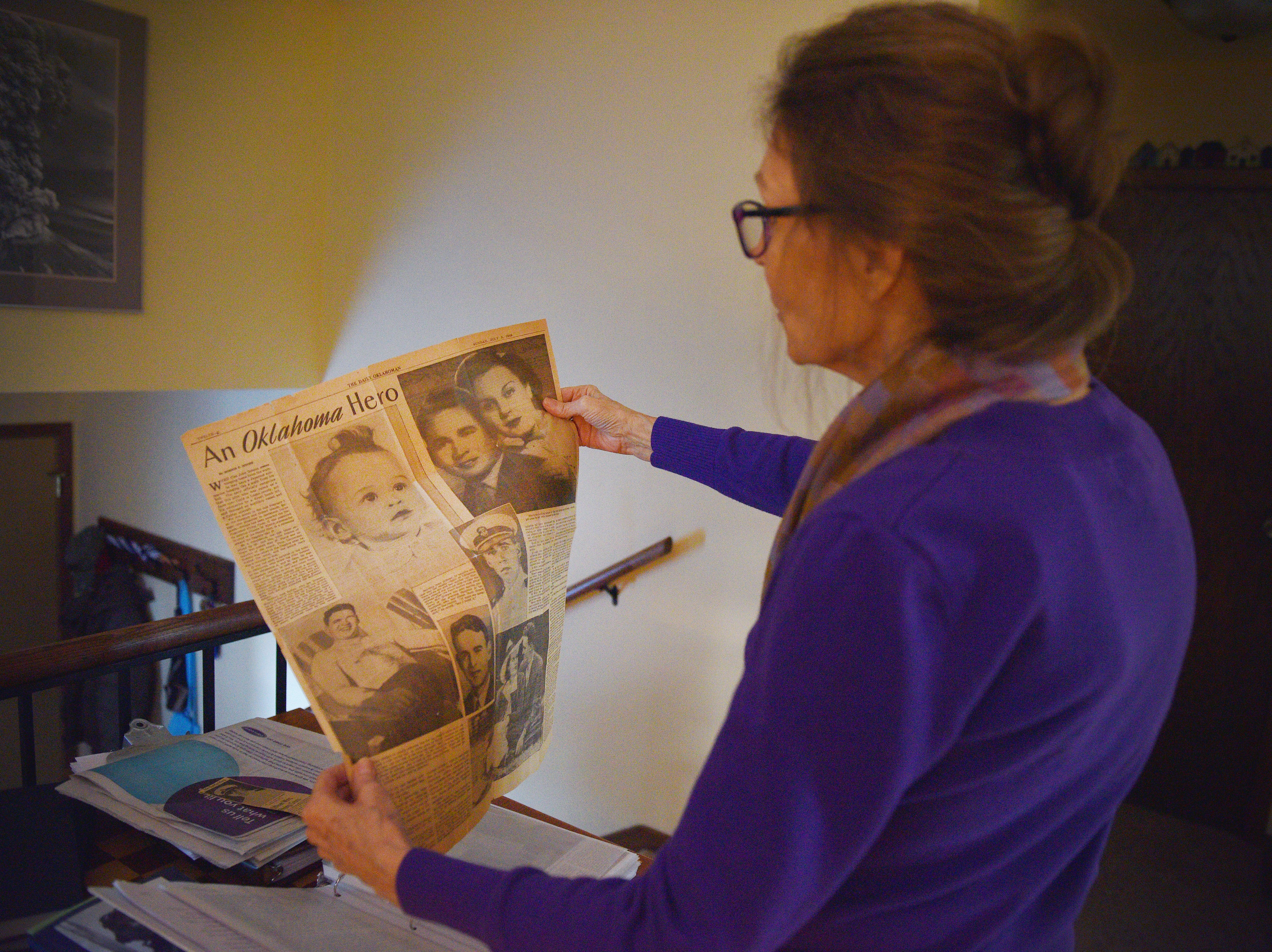 Nancy Napier looks at old newspaper clippings of her father, Cleo Dobson, Wednesday Dec. 5, in Sioux Falls. Napier's father was a U.S. Navy carrier pilot in World War II. Napier and her cousin, Carl Dobson, published the book  ÒCleo J. Dobson: U.S. Navy Carrier Pilot World War II, a Personal Account.Ó