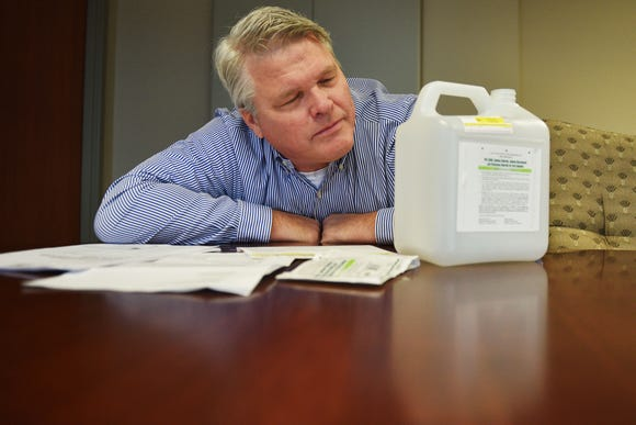 """Stu Whitney talks about the four-liter jug of """"prep solution"""" consisting of sodium chloride and sodium bicarbonate that he had to drink prior to getting a colonoscopy Thursday, Dec. 6, at the Argus Leader newsroom in Sioux Falls."""