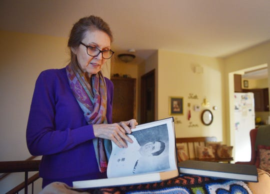 Nancy Napier looks at photos of her father, Cleo Dobson, Wednesday Dec. 5, in Sioux Falls. Napier's father was a U.S. Navy carrier pilot in World War II. Napier and her cousin, Carl Dobson, published the book  ÒCleo J. Dobson: U.S. Navy Carrier Pilot World War II, a Personal Account.Ó
