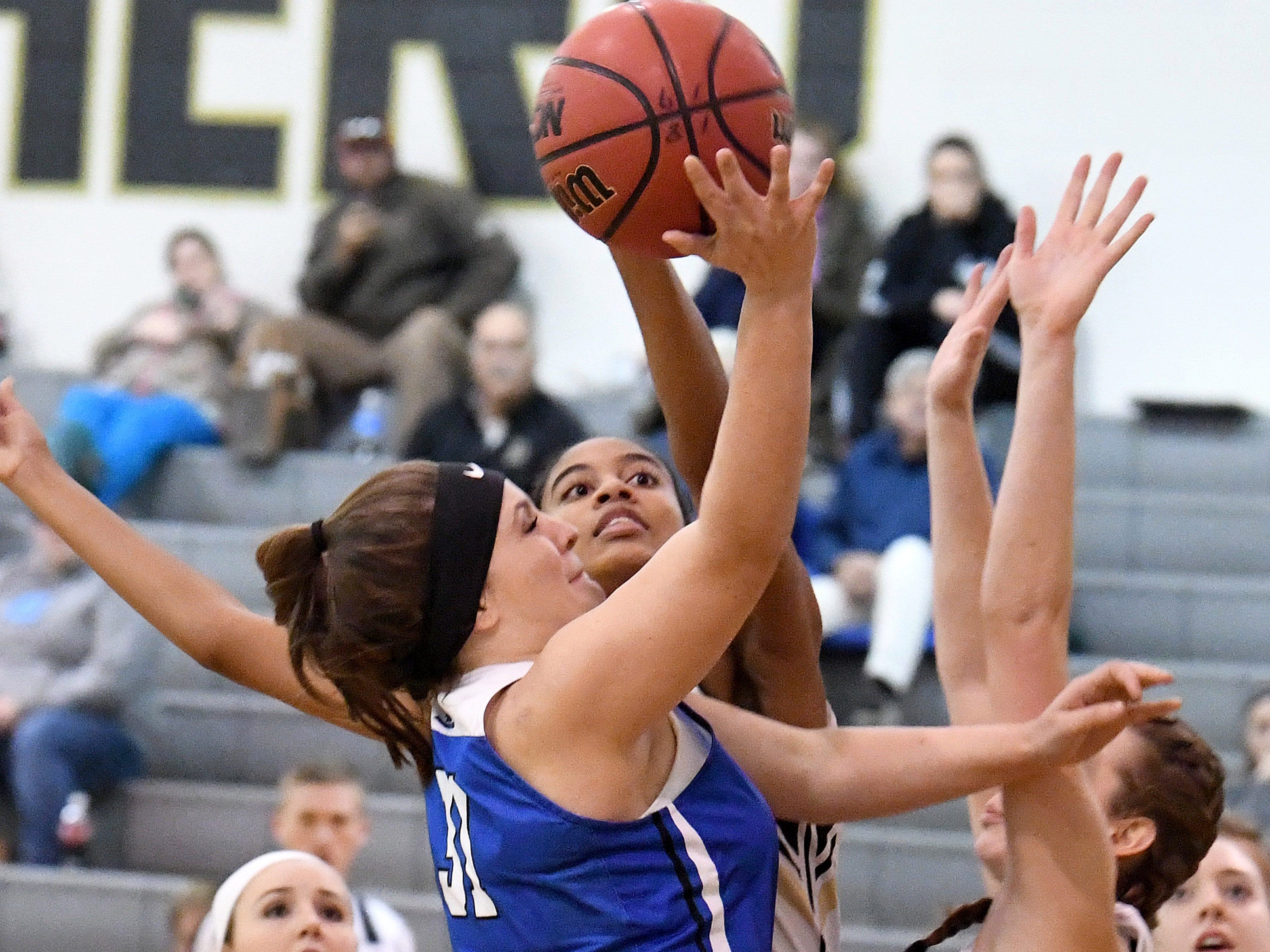 Buffalo Gap's Amaya Lucas (center) looks to block a shot by Fort Defiance's Cailin Wright (left) who tries to reach the basket with the ball during a game played in Swoope on Wednesday, Dec. 5, 2018.