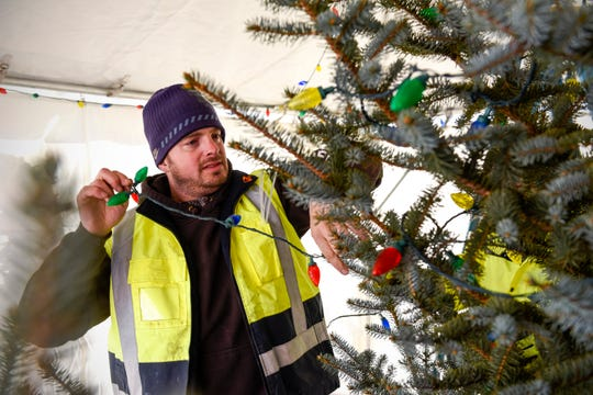 St. Cloud Public Works employee Matthew Traut strings lights on the official tree Thursday, Dec. 6, 2018, for the annual Weihnachtsmarkt.