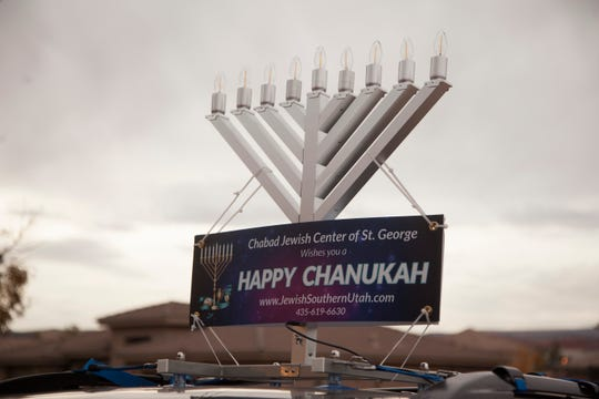 Rabbi Mendy drives with a menorah on his car to share the meaning of Hanukkah to the community Wednesday, Dec. 5, 2018.