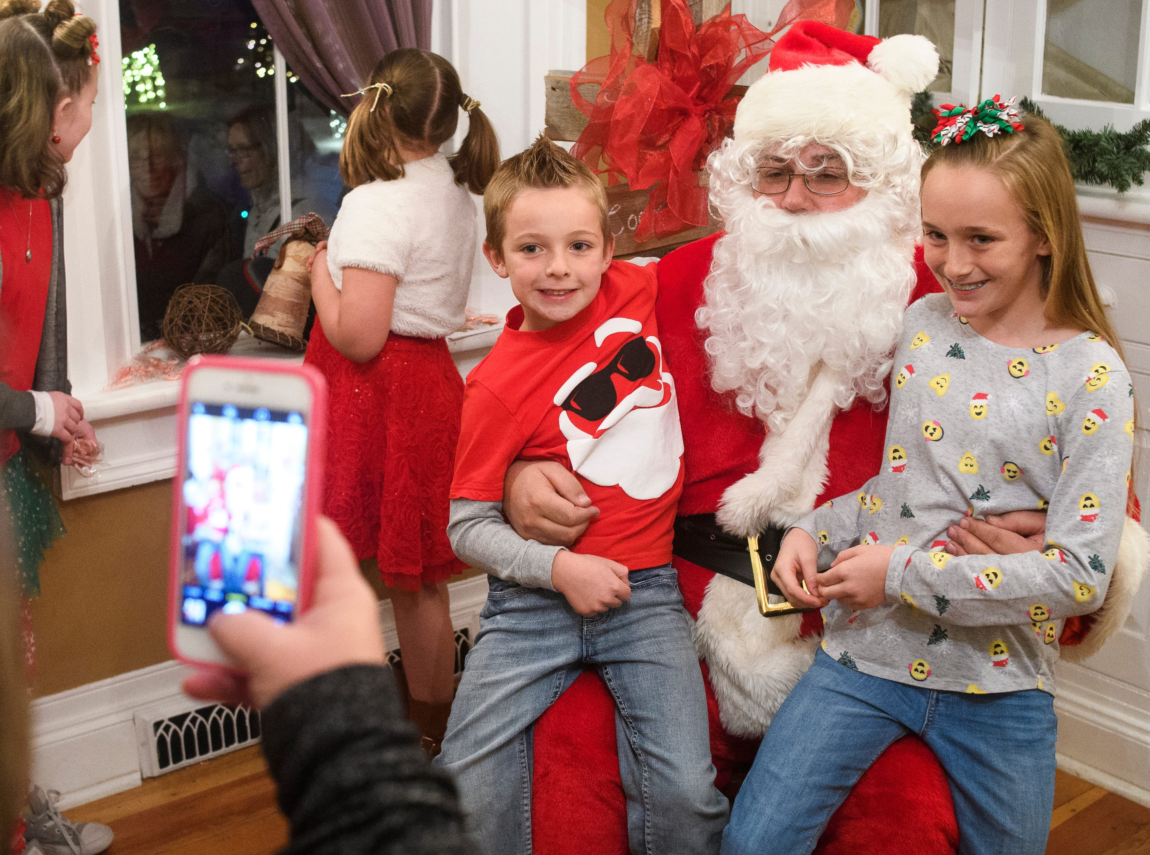 Carson (L) and Lexi Zavoico (R) visit with Santa Claus during Christmas at the Homestead in Frontier Homestead State Park Wednesday, December 5, 2018. The event included live music and crafts.