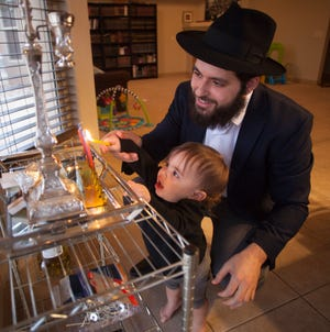 Rabbi Mendy Cohen and his son light the menorah during Hanukkah on Wednesday, Dec. 5, 2018.