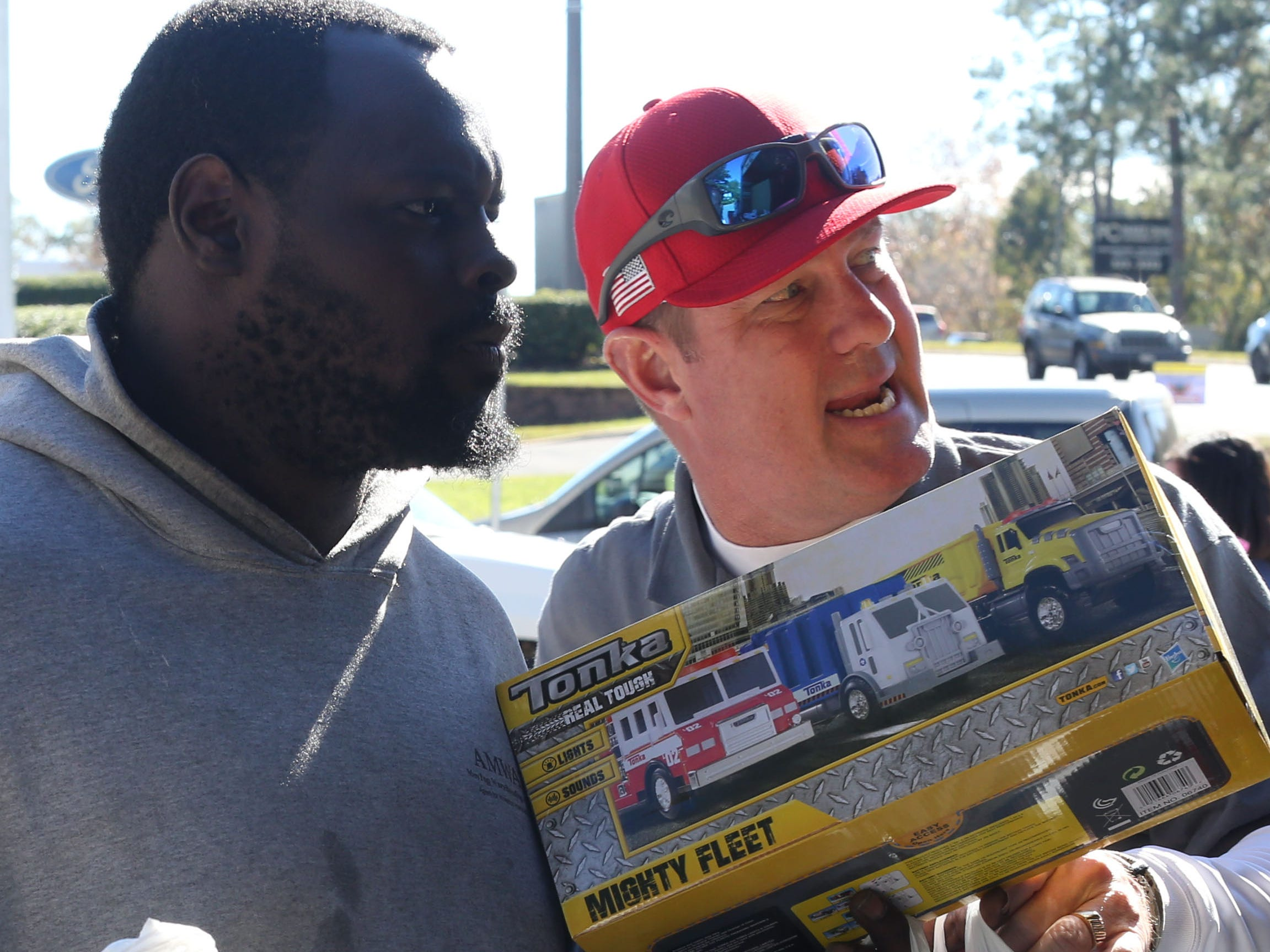 Frank Grims, warehouse manager at A.M.W.A.T. Moving and Warehouse, left, and Dean Pugh, owner of A.M.W.A.T. Moving and Warehouse, load toys into a moving truck for the toy drive for children impacted by Hurricane Michael hosted by Rebuild 850 outside of the Tallahassee Democrat, Thursday, Dec. 6, 2018.