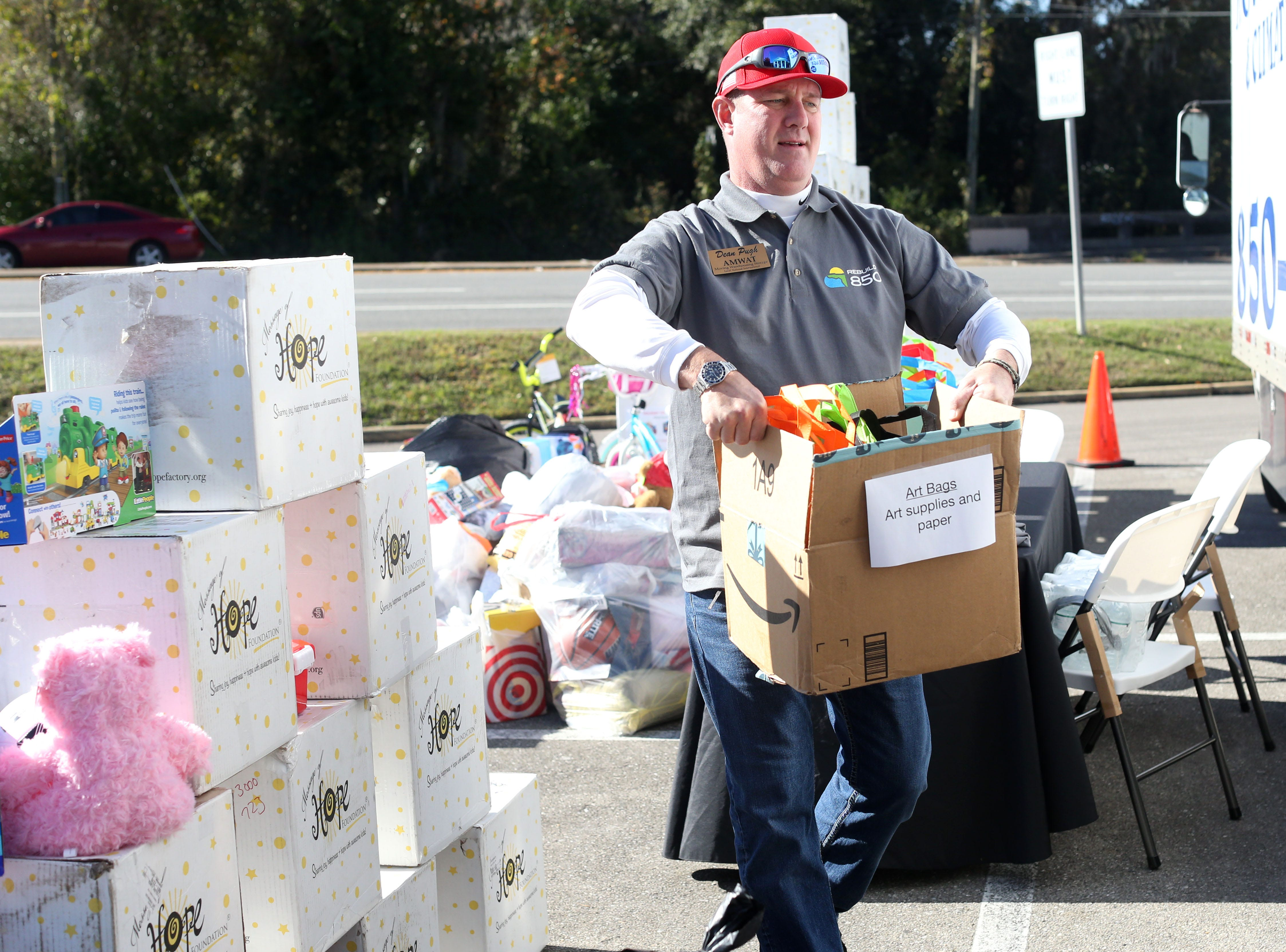 Dean Pugh, owner of A.M.W.A.T. Moving and Warehouse, loads toys into a moving truck for the toy drive for children impacted by Hurricane Michael hosted by Rebuild 850 outside of the Tallahassee Democrat, Thursday, Dec. 6, 2018.